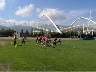 τα παιδιά στο summer camp παίζουν ποδόσφαιρο στο ανοικτό ολυμπιακών διαστάσεων γήπεδο στο οακα