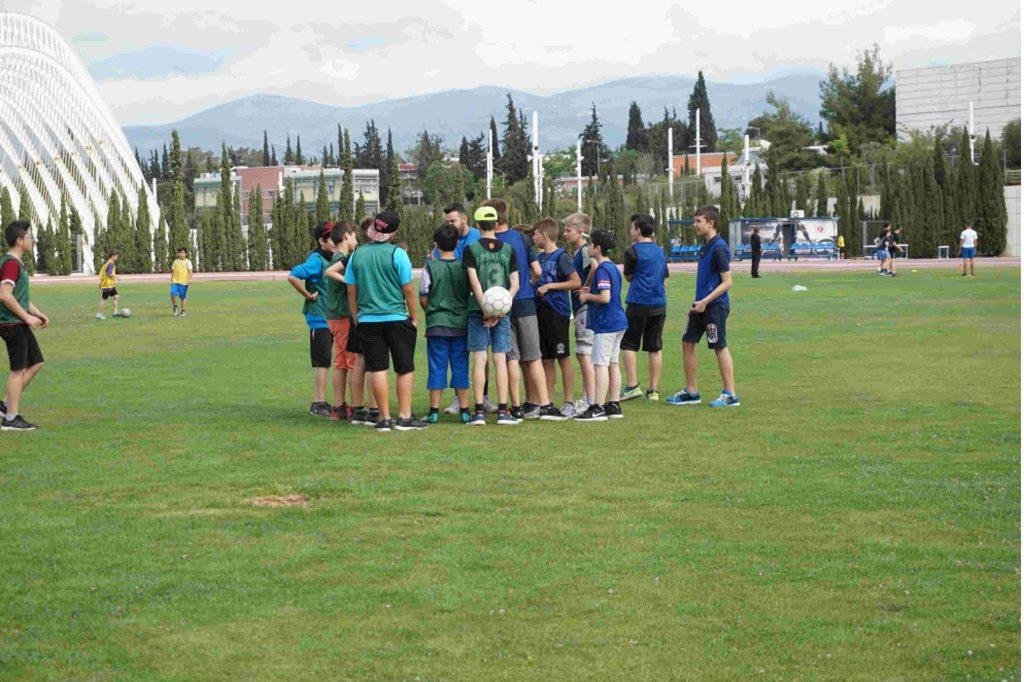 μεγάλη ομάδα μαθητών συγκεντρωμένοι το κέντρου του ποδοσφαιρικού γηπέδου στη σχολική τους εκδρομή στο οακα