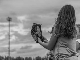 ασπρόμαυρη φωτογραφία μίας μαθήτριας, στη σχολική της εκδρομή στο ΟΑΚΑ φοράει γάντι softball και κρατάει τη μπάλα του softball