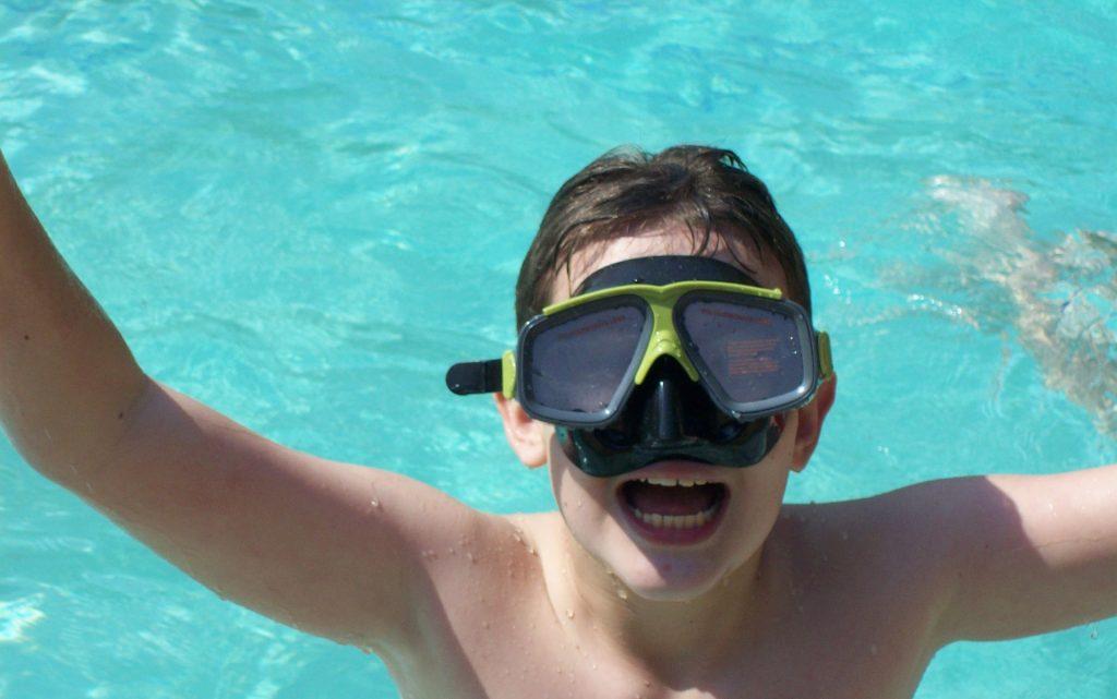 παιδί με μάσκα κολύμβησης μέσα στη πισίνα στο καλοκαιρινό καμπ στο οακα