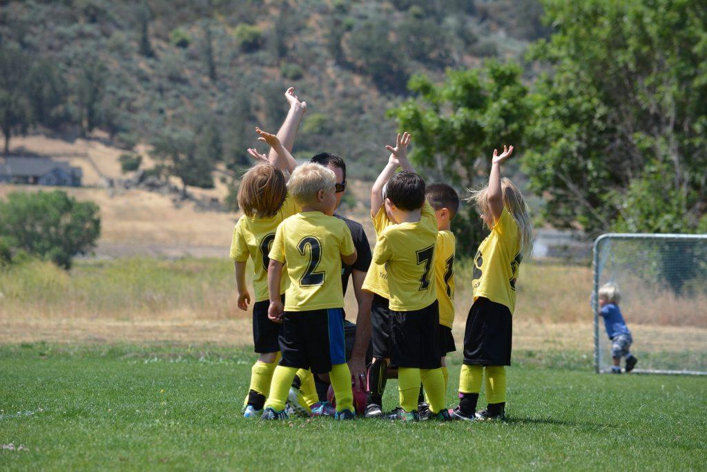 ομάδα από μικρής ηλικίας παιδιών συμμετέχουν στο καλοκαιρινό καμπ και παίρνουν τις τελευταίες συμβουλές του προπονητή τους, για να παίξουν ποδόσφαιρο