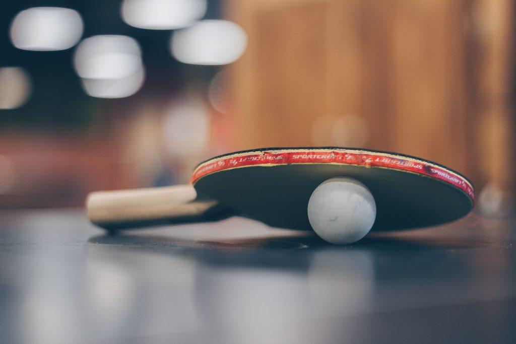 ρακέτα ping-pong και απο κατω απο τη ρακέτα είναι ένα άσπρο μπαλάκι ping pong