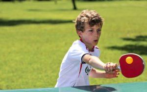 ενα παιδί παίζει ping-pong και με τηξ ρακετα του χτυπάει το κιτρινο μπαλάκι του ping pong